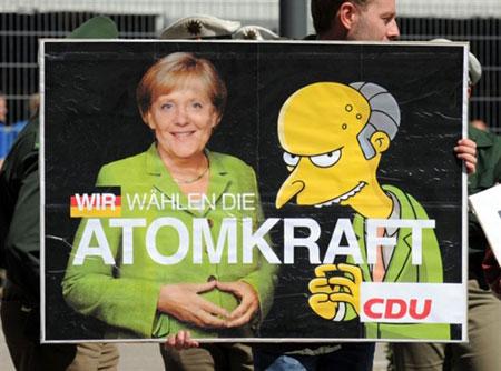 Un manifestante sostiene un cartel comparando a Frau Merkel y Mr Burns